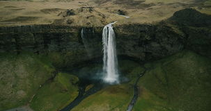 Copter flying away from the Seljalandsfoss waterfall. Turbulent flows of water falls down from the mountain in Iceland. Beautiful aerial landscape of the stock footage