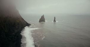Copter flying over the beautiful black volcanic beach and troll toes cliffs in Iceland. Landscape of sea, fog and waves. stock footage