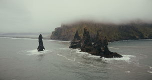 Copter turning around the troll toes cliffs on the sea in Iceland. Beautiful black volcanic beach and mountain in fog. stock footage