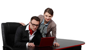 COpule on a Notebook. Young casual couple looking to a red notebook on a black desk, isolated against a white background Royalty Free Stock Image