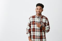 Copy space for advertisement. Dark-skinned young good-looking joyful man with curly hairstyle in checkered shirt Royalty Free Stock Photography