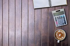 Copy space blank book and coffee and calculator on wood of brown. Top view stock image