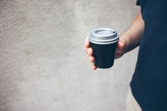 Man is holding black cup of take-away coffee, concrete wall texture on the background Stock Photography