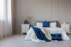 Copy space on grey wall of scandinavian bedroom interior with blue, white and grey design. Copy space on empty grey wall of scandinavian bedroom interior with stock images