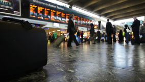 Copy space: Euston train station. LONDON, UK - 23 MARCH 2015: Video footage with shallow focus on the foreground briefcase sitting on the floor of the concourse stock video