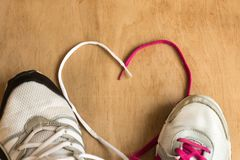 Man and woman fashion trendy trainers with lace heart on wooden background. stock images