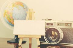 Copy space,flat lay composition of vintage camera,globe, easel and canvas frame on wooden table. Ideal for vacation and travel concept Stock Images