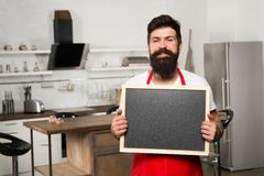 Copy space at his board. Man chef with board, copy space. Mature male. Bearded man cook. Restaurant or cafe menu royalty free stock photos