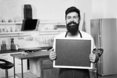 Copy space at his board. Man chef with board, copy space. Mature male. Bearded man cook. Restaurant or cafe menu. Advertisement. Hipster in kitchen. Bearded stock image
