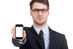 Copy space on his mobile phone. Portrait of confident young man in formalwear stretching out mobile phone and looking at camera while standing isolated on white Royalty Free Stock Images