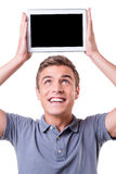 Copy space on his tablet. Happy young man holding digital tablet upon his head and smile while standing isolated on white background Stock Image