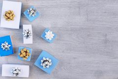 Copy space on a light wooden background. White and blue gift boxes with beautiful bows. Festive Christmas composition. royalty free stock photo
