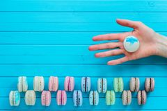 Copy space - macaroon or macaron in the girl`s hand on a wooden turquoise background. Suggest to try almond cookies.  Royalty Free Stock Photography