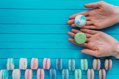 Copy space - macaroon or macaron lies in the hands of a girl on a wooden turquoise background, an offer to try almond. Cookies Stock Images