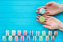 Copy space - macaroon or macaron lies in the hands of a girl on a wooden turquoise background. Offer to try almond. Cookies Royalty Free Stock Image