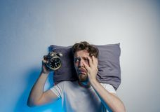 Copy space, man having trouble sleeping. Sad face, looking at old fashion alarm clock stock photo
