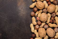 Copy space with nuts in a shell. Walnuts, hazelnuts and peanuts on dark background. Tasty healthy snack, food. Copy space with nuts in a shell. Walnuts royalty free stock photos