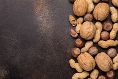 Copy space with nuts in a shell. Walnuts, hazelnuts and peanuts on dark background. Tasty healthy snack, food. Copy space with nuts in a shell. Walnuts stock photos