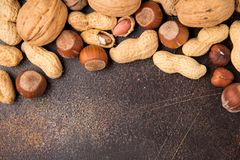 Copy space with nuts in a shell. Walnuts, hazelnuts and peanuts on dark background. Tasty healthy snack, food. Copy space with nuts in a shell. Walnuts royalty free stock images