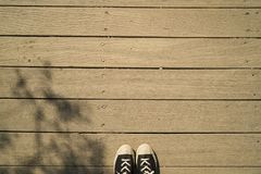 Copy space for sneakers journey travel lifestyle with black and white shoes, wooden plank strips grain floor and tree shadow Royalty Free Stock Image