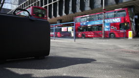 Copy space: suitcase at bus terminal. LONDON, UK - 23 MARCH 2011: Video footage with shallow focus on the foreground suitcase sitting on the pavement outside a stock video