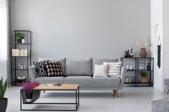 Copy space on the wall of scandinavian living room with modern couch, metal shelves and industrial coffee table. Real photo stock images