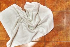 Copy space. Wet creased white towel on ceramic floor in bathroom. Ceramic tile warm colors, for background. royalty free stock images