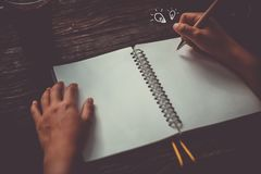 Copy space of woman hand writing down in white notebook with idea icon. stock photos