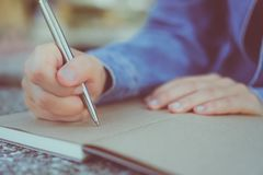 Copy space of woman hand writing down in white notebook with sun light background. stock image