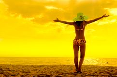 Copy space of woman rise hand up on sunset sky at beach stock image