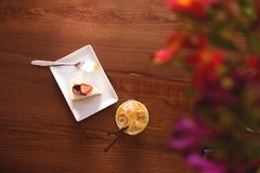 Abstract background with cake with strawberries and cold cup of coffee on a wooden table stock photography