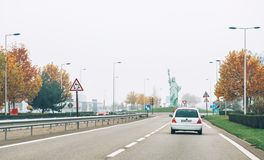 Copy of Statue of Liberty made by Auguste Bartholdi. COLMAR, FRANCE - NOV 23, 2014: Driver point of vew towar the copy of Statue of Liberty made by Auguste Stock Photos