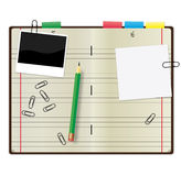 Copybook. Open copybook with a green pencil, photograph and paper clips Stock Photo