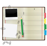 Copybook. Open copybook with a green pencil, photograph and paper clips Royalty Free Stock Images
