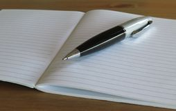 Copybook and pen. A black and silver pen over empty pages Stock Image