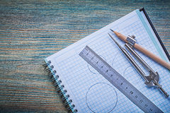 Copybook ruler pair of compasses pencil on vintage wooden board Royalty Free Stock Photo