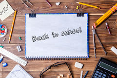 Copybook with text - back to school and student material on wooden table. Royalty Free Stock Photo