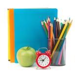 Copybooks z zielonym jabłkiem i budzikiem Fotografia Stock