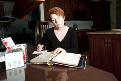 Copying Recipes. Mature woman sitting in kitchen copying recipes from cookbook royalty free stock image