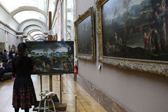 Copyist painter at work, The Louvre, Paris, France. PARIS, FRANCE, MARCH 27, 2017 : copyist painter at work in the great gallery at the Louvre museum, march 27 Royalty Free Stock Images