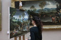 Copyist painter at work, The Louvre, Paris, France. PARIS, FRANCE, MARCH 27, 2017 : copyist painter at work in the great gallery at the Louvre museum, march 27 Stock Image