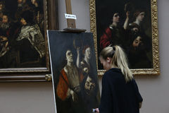 Copyist painter at work, The Louvre, Paris, France. PARIS, FRANCE, MARCH 27, 2017 : copyist painter at work in the great gallery at the Louvre museum, march 27 Stock Photo