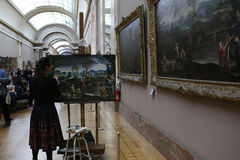 Copyist painter at work, The Louvre, Paris, France. PARIS, FRANCE, MARCH 27, 2017 : copyist painter at work in the great gallery at the Louvre museum, march 27 Stock Photos