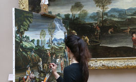 Copyist painter at work, The Louvre, Paris, France. PARIS, FRANCE, MARCH 27, 2017 : copyist painter at work in the great gallery at the Louvre museum, march 27 Royalty Free Stock Image
