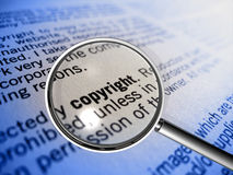 Copyright in focus. A magnifier focusing on the word copyright in small print Stock Image