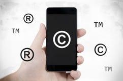 Copyright, símbolos da marca registrada que voam em torno do smartphone fotos de stock
