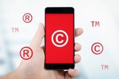 Copyright, simboli di marchio di fabbrica che volano intorno allo smartphone Fotografia Stock Libera da Diritti
