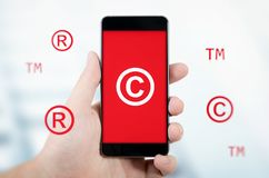 Copyright, trademark symbols flying around smartphone. Security and piracy composition Royalty Free Stock Photo