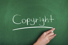 Copyright. Woman hand writing Copyright on chalkboard Royalty Free Stock Photo