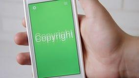 Copyrights l'applicazione di concetto sullo smartphone L'uomo usa il cellulare app stock footage